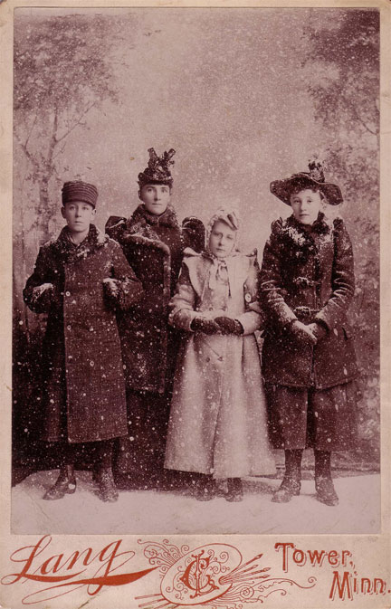 Fashionable winter clothes were readily available on Lake Vermilion in the 1890s. Tower, Minnesota merchants were always ready to provide the latest New York City styles for their northwoods consumers. The Wallace family, sporting their new winter garments, stopped to pose for a cabinet photograph at Charles Lang's studio in Tower. —photo c. 1890